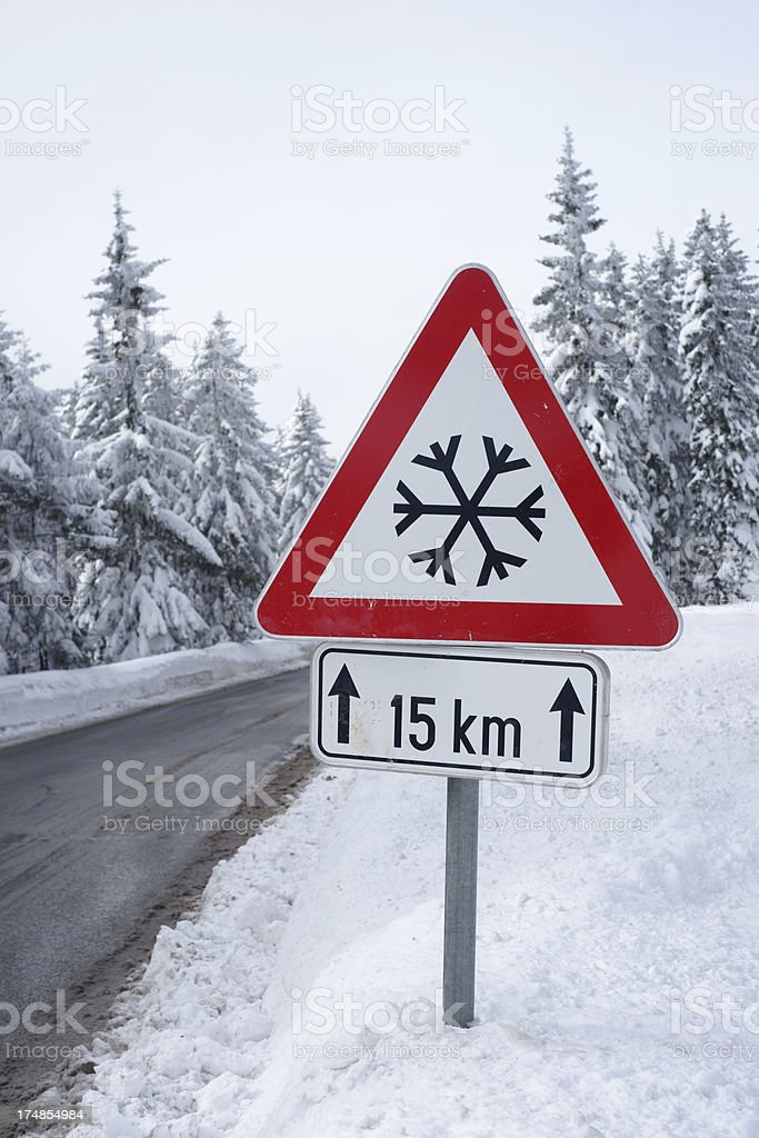 Road in winter with traffic sign - vertical royalty-free stock photo