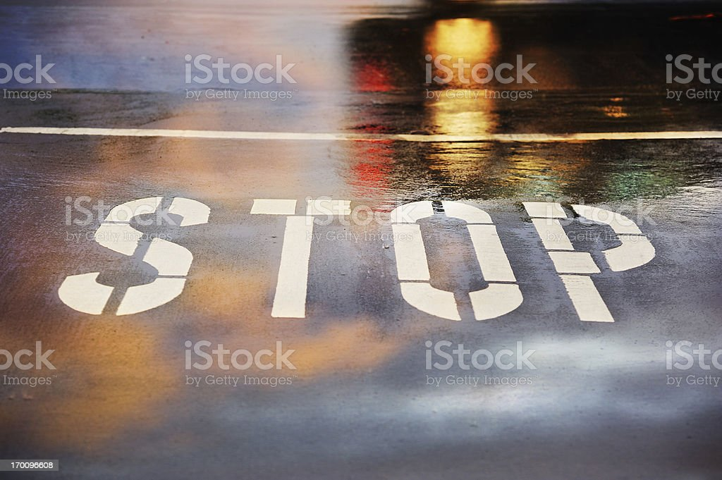 Road junction, stop word, motion blurred car in pouring rain stock photo