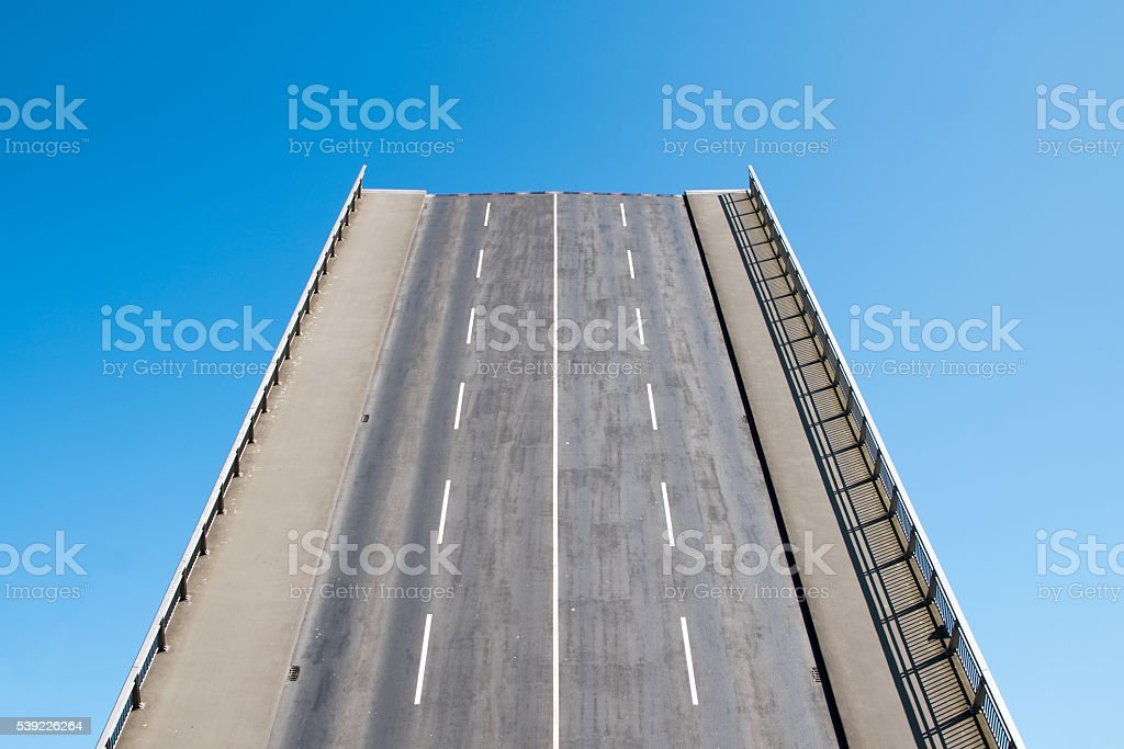 Road leads directly upwards in the blue sky, future concept stock photo