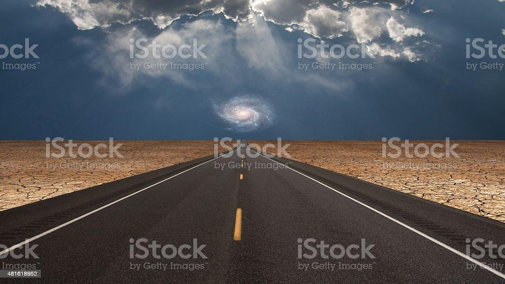 Road leads into desert toward galaxy above horizon stock photo