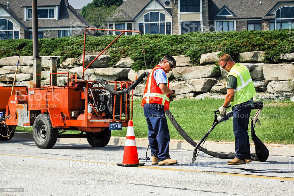 Road maintenance workers fixing the cracks and potholes stock photo