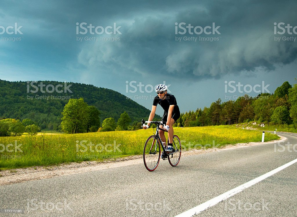 Road male cyclist against the thundercloud stock photo