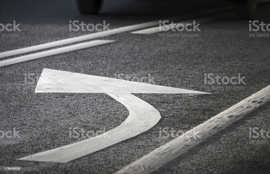 Road marking. White turning arrow and lines on dark asphalt. stock photo