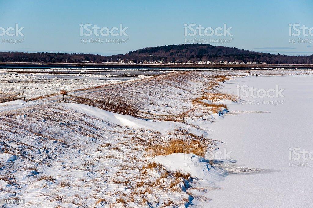 Road on dike that crosses marsh stock photo