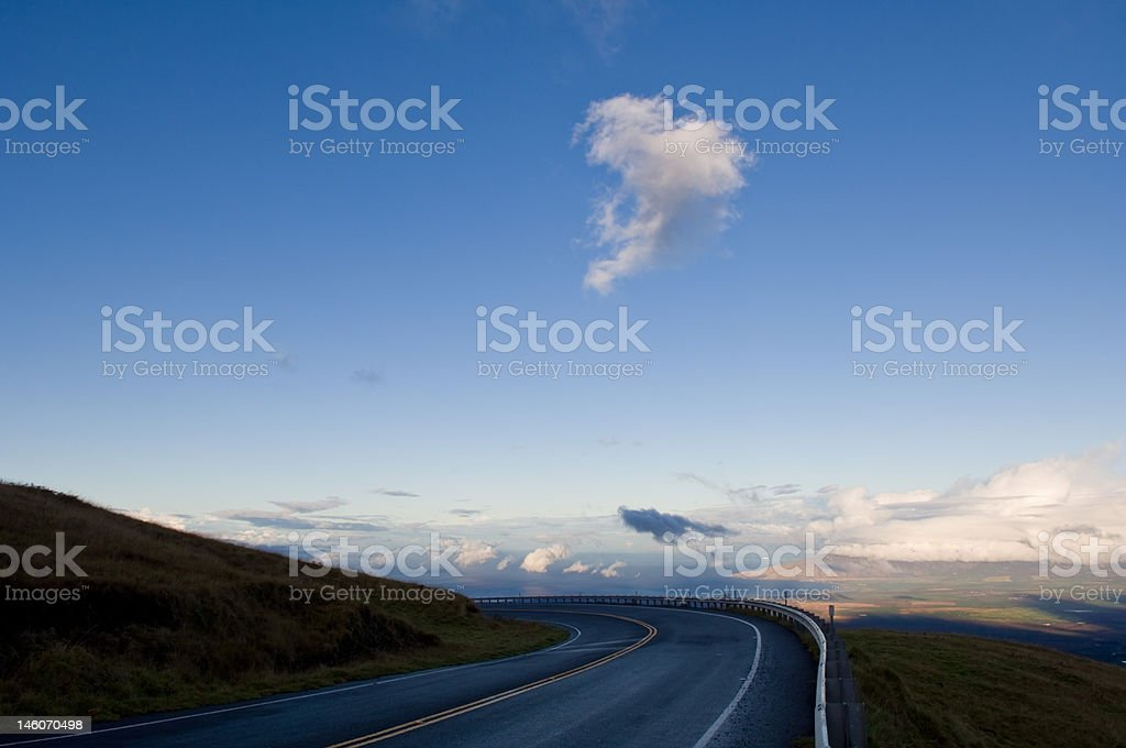 Road on mountain side with lone cloud rising above stock photo