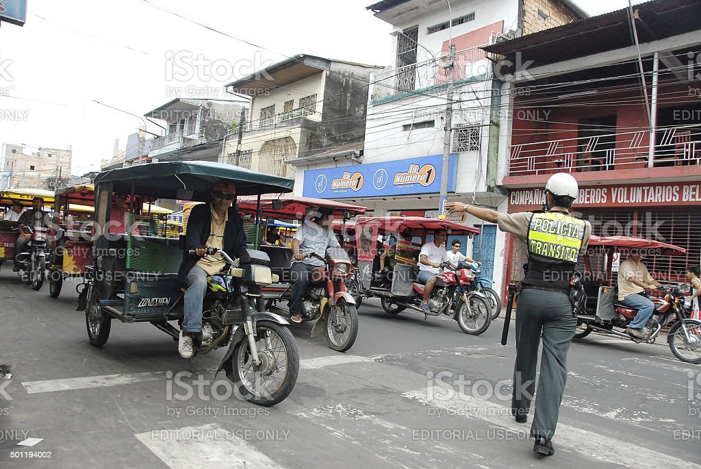 Road policewoman regulates city traffic in Iquitos, Peru. stock photo