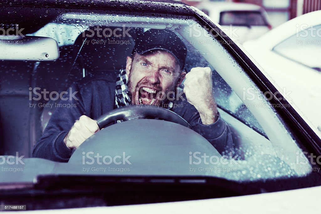 Road rage! Angry male driver roaring with frustrated fury. stock photo