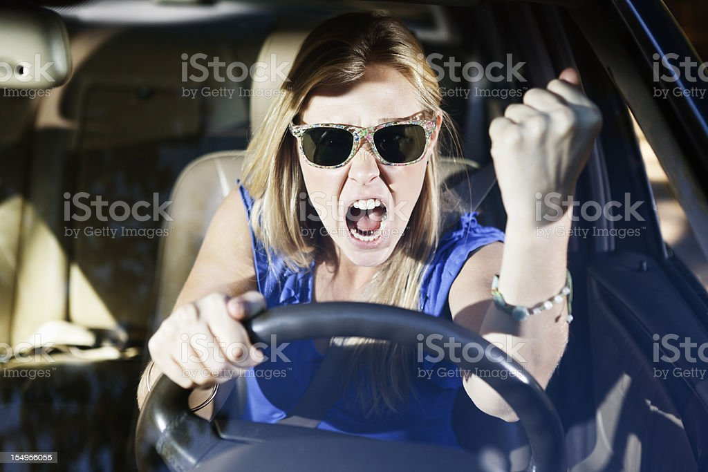 Road rage! Beautiful blonde driver shakes her fist in fury royalty-free stock photo