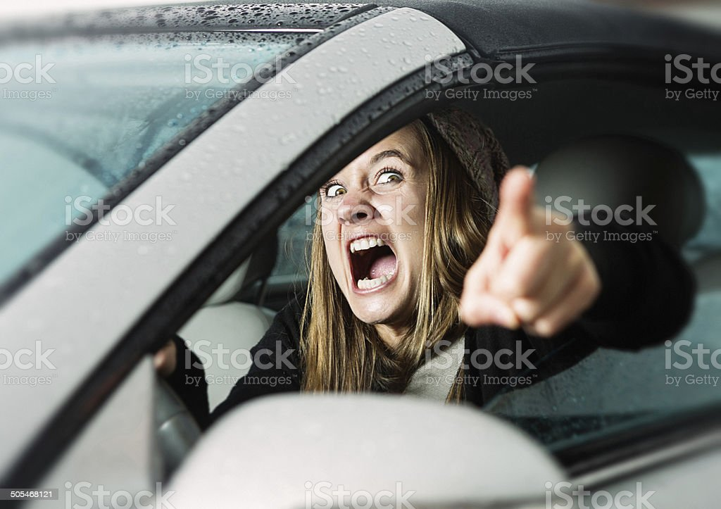 Road rage! Enraged young woman driver shouts and points accusingly. stock photo