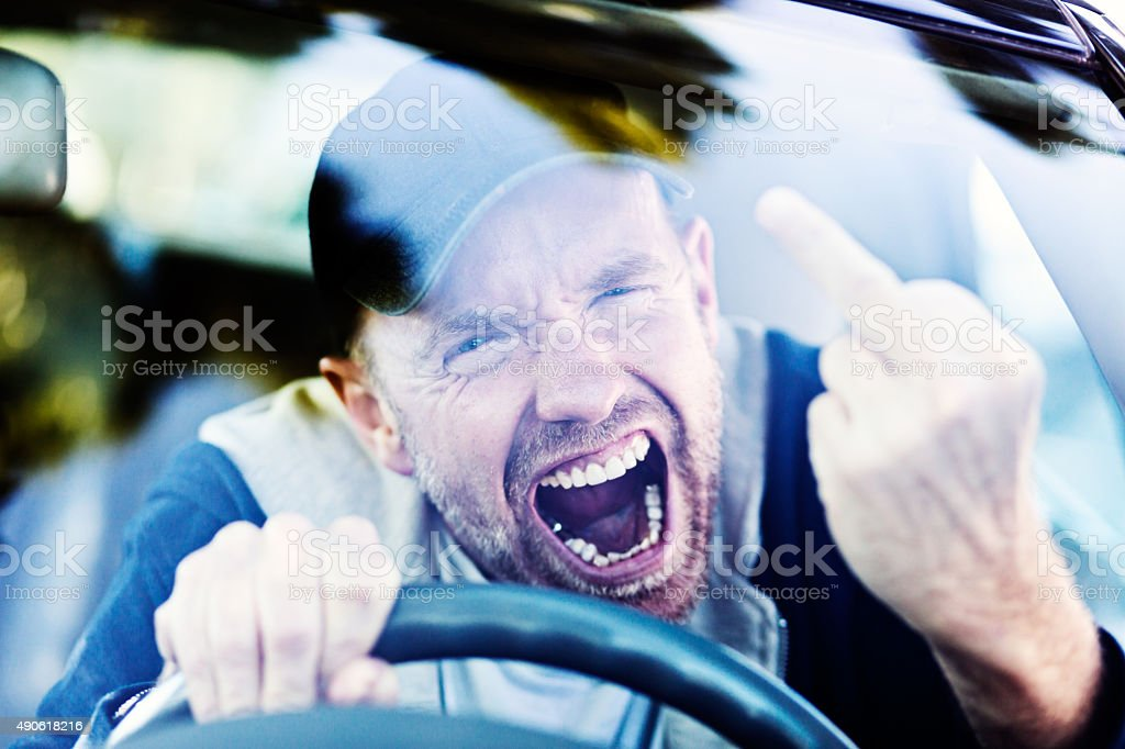 Road rage: furious male driver makes obscene gesture, yelling stock photo