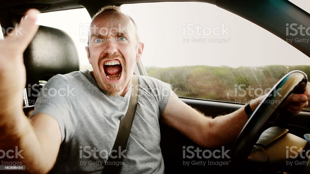 Road rage: furious male driver shouting, waving, and yelling stock photo