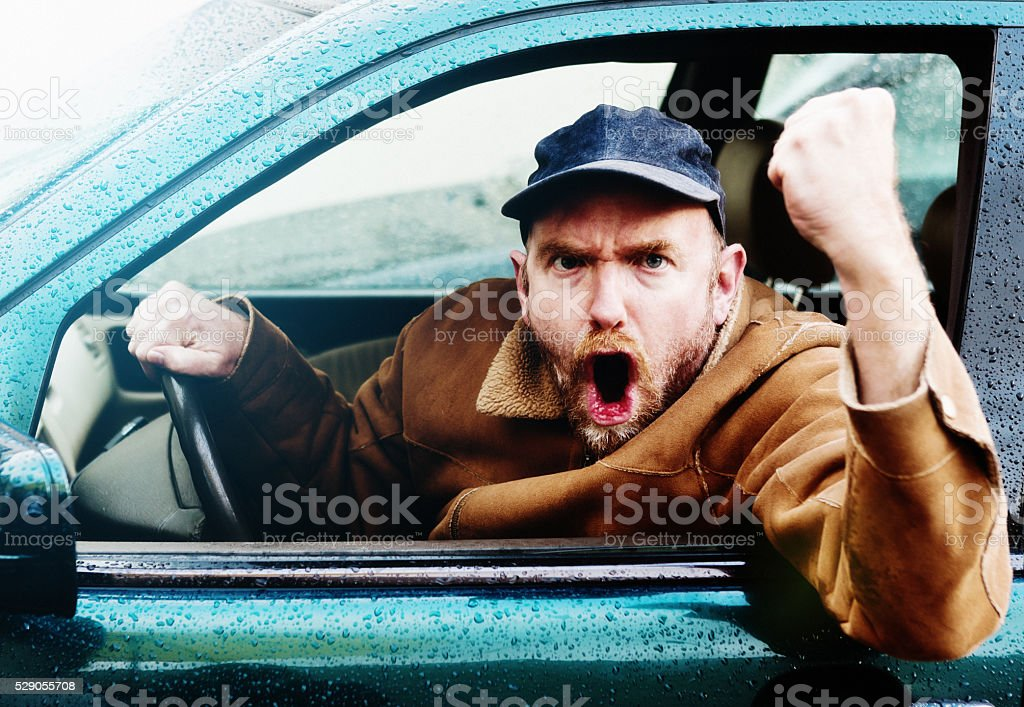 Road rage: Furious male driver yelling, shaking fist through window stock photo