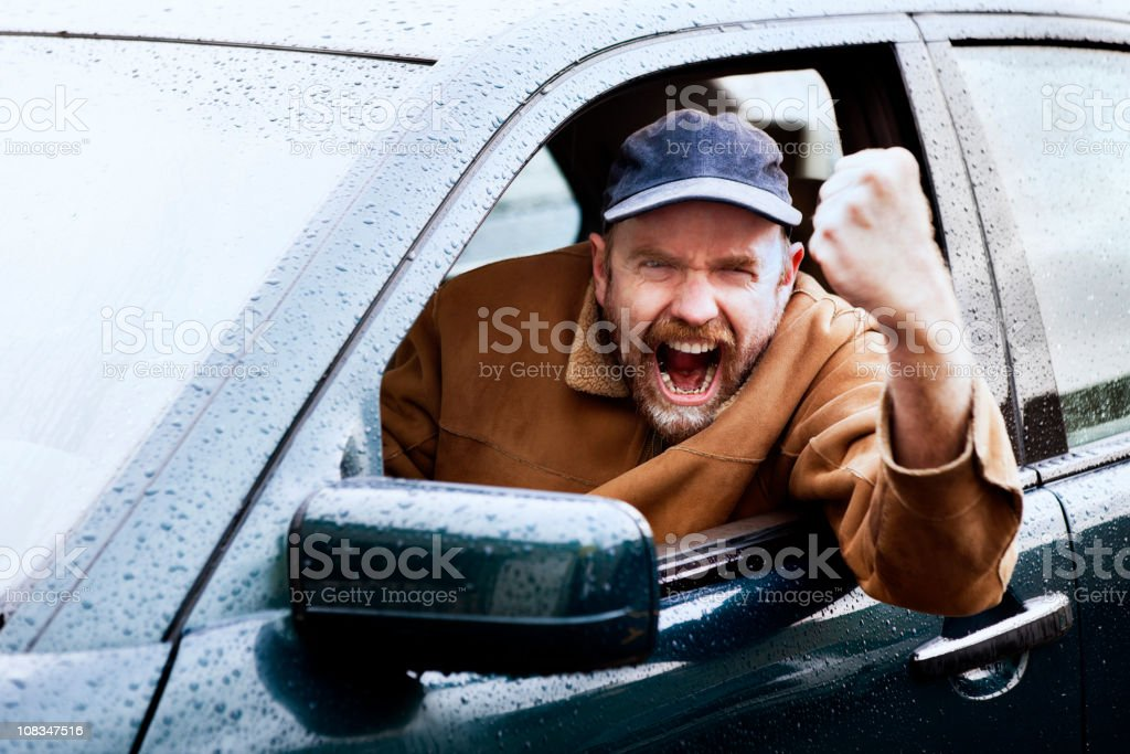 Road rage rules with this infuriated driver shaking his fist stock photo