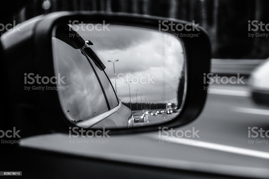 Road reflected in side mirror of car stock photo