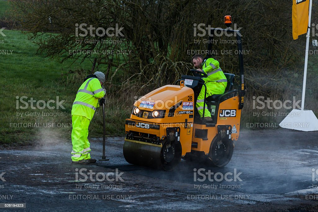 Road repair, Small JCB steam roller levels the tarmac. Two road...