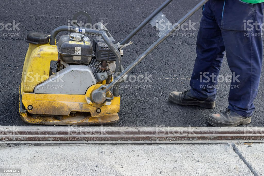 road repairing with vibrating compactor plate stock photo