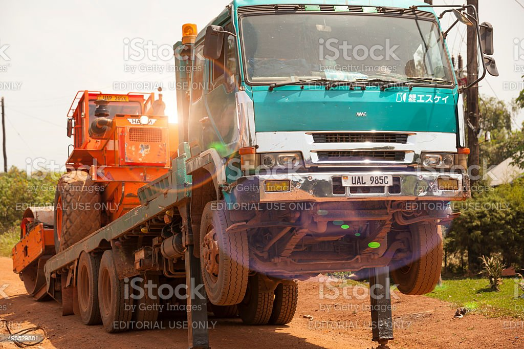 Road Roller moving down from truck stock photo