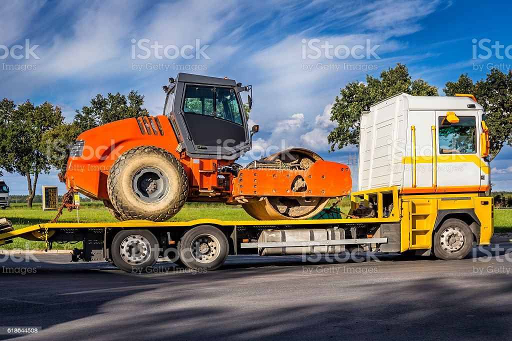 Road roller on the truck trailer stock photo