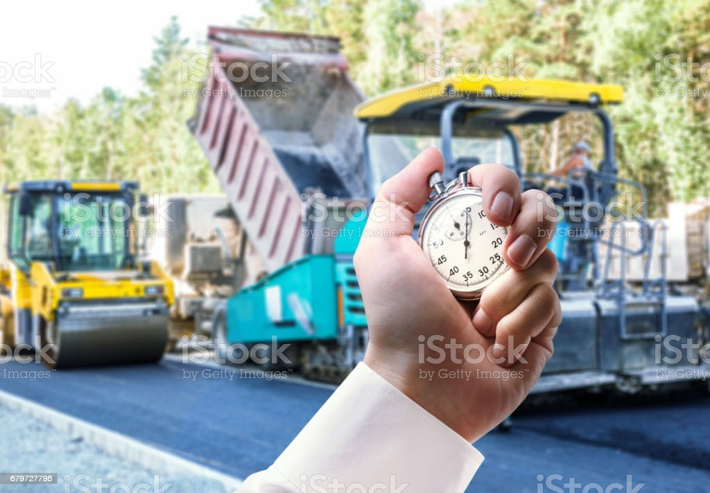 Road roller working and stopwatch in hand stock photo