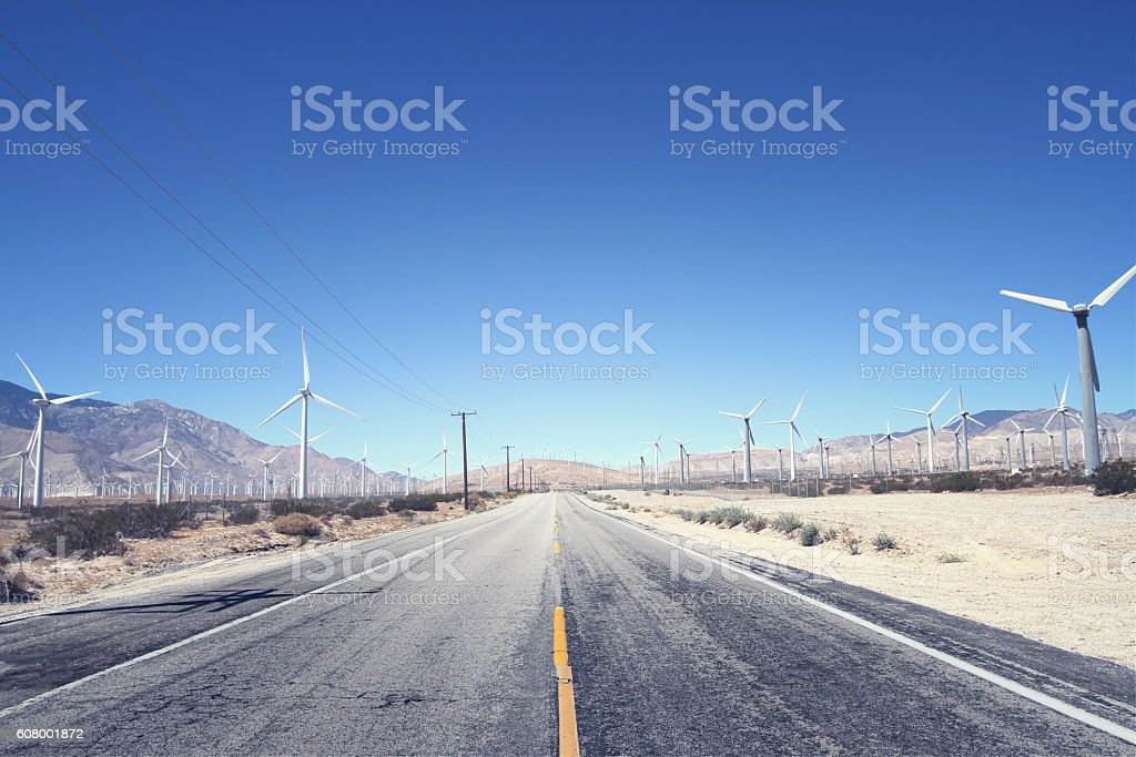 Road running through a wind turbine farm stock photo