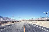 Road running through a wind turbine farm