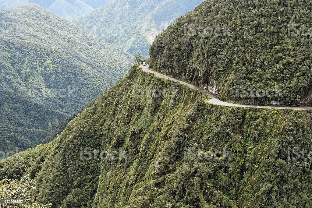 A road running through a wooded mountain royalty-free stock photo