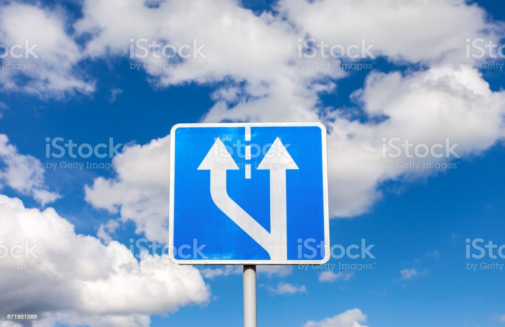 Road sign against the blue sky with clouds stock photo