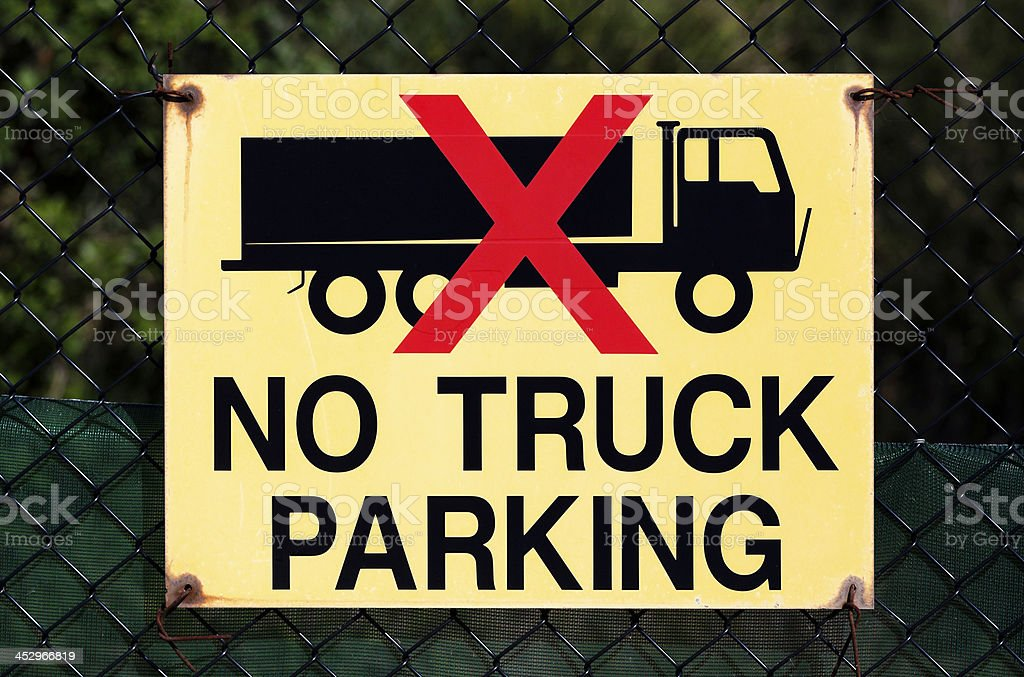 Road sign 'NO TRUCK PARKING' against dark background royalty-free stock photo