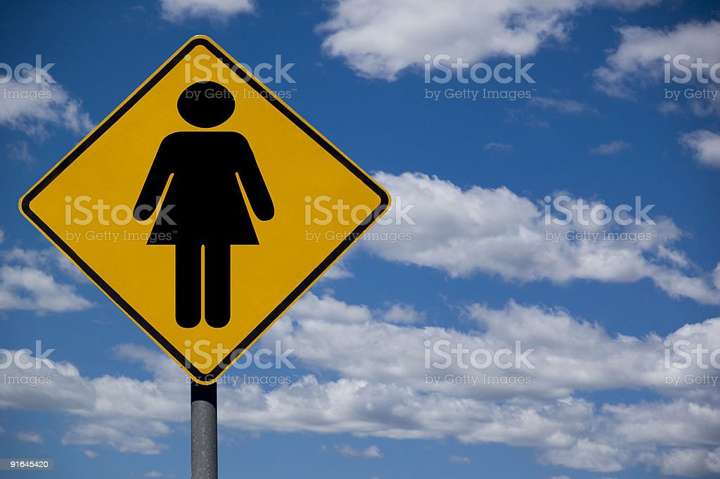 Road sign of female silhouette against bright sky royalty-free stock photo