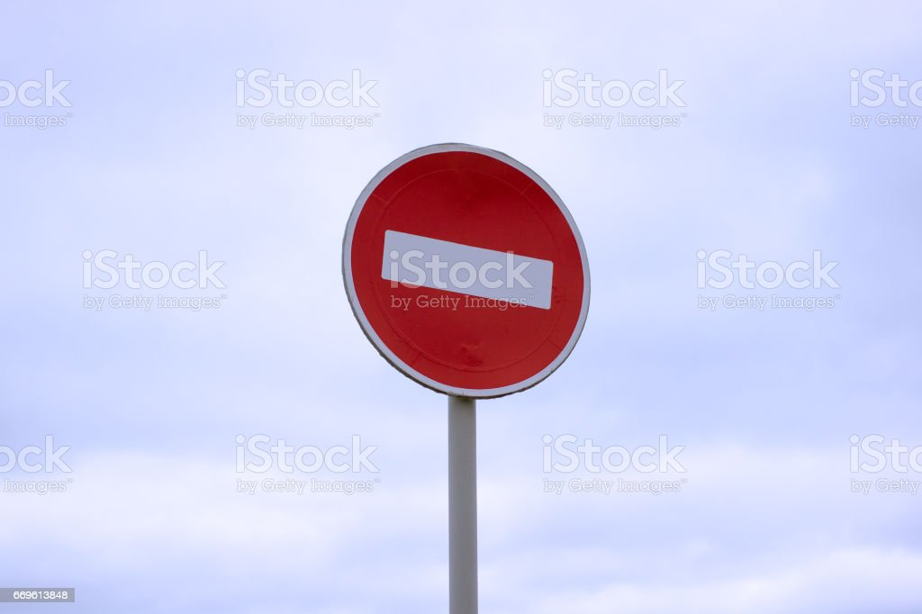 Road sign prohibiting the entry of cars against the blue sky and clouds stock photo