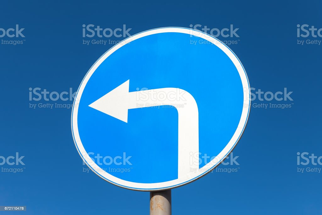 Road sign Turn left against the blue sky stock photo