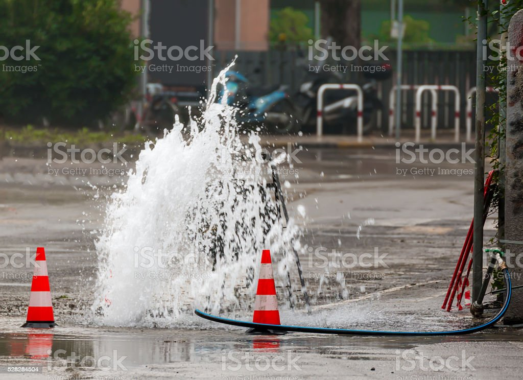 road spurt water beside traffic cones stock photo