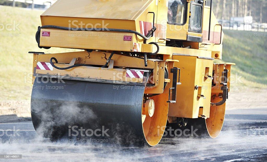 A road steam roller on a foggy asphalt stock photo