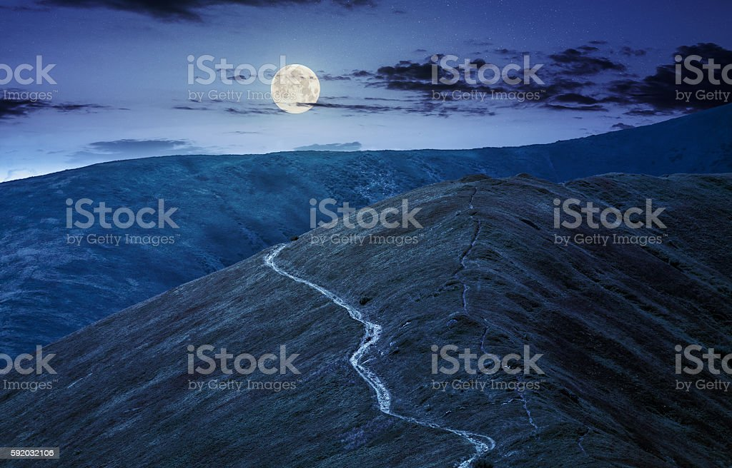 road through a meadow on hillside at night stock photo