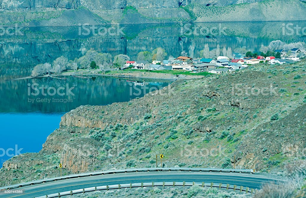 Road through basalt formations to town on river in Washington stock photo