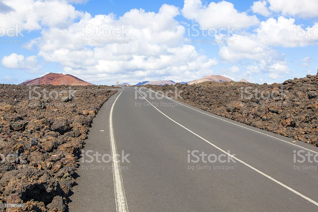 Road through lava rocks and volcanic mountains. Los Hervideros. stock photo
