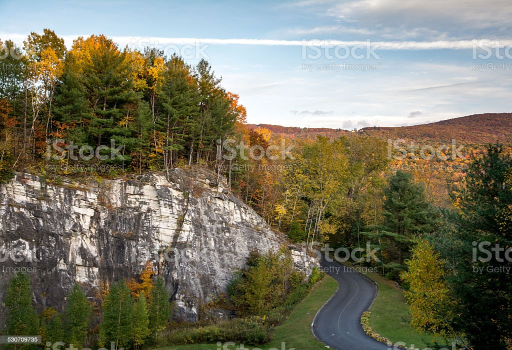 Road through thick fall foliage and marble rock formation stock photo