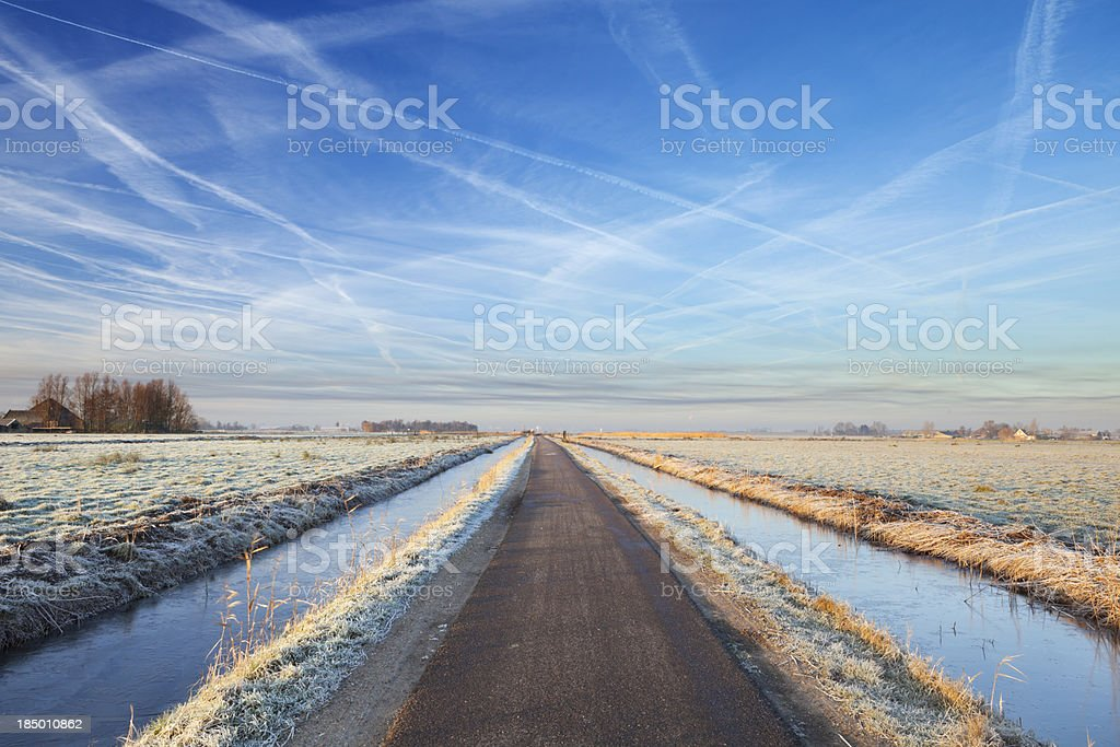 Road through typical Dutch polder landscape in winter at sunrise royalty-free stock photo