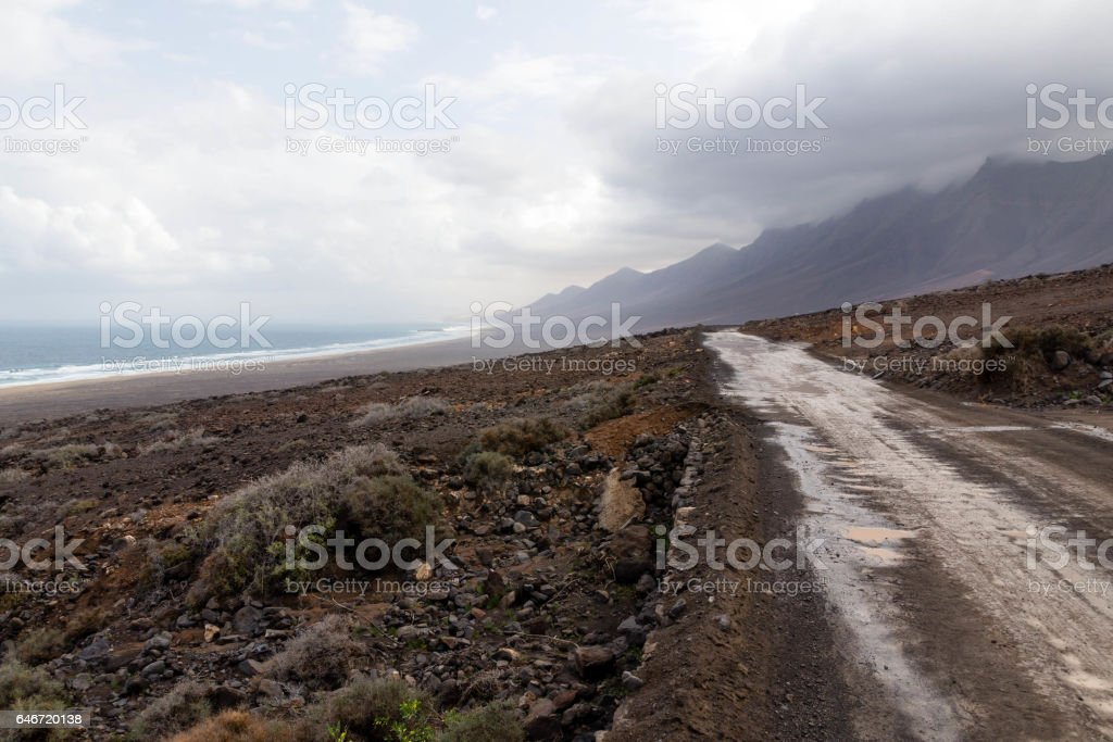 Road to Cofete Beach with mountains in the clouds - Jandia, Fuerteventura, Canary Islands, Spain stock photo