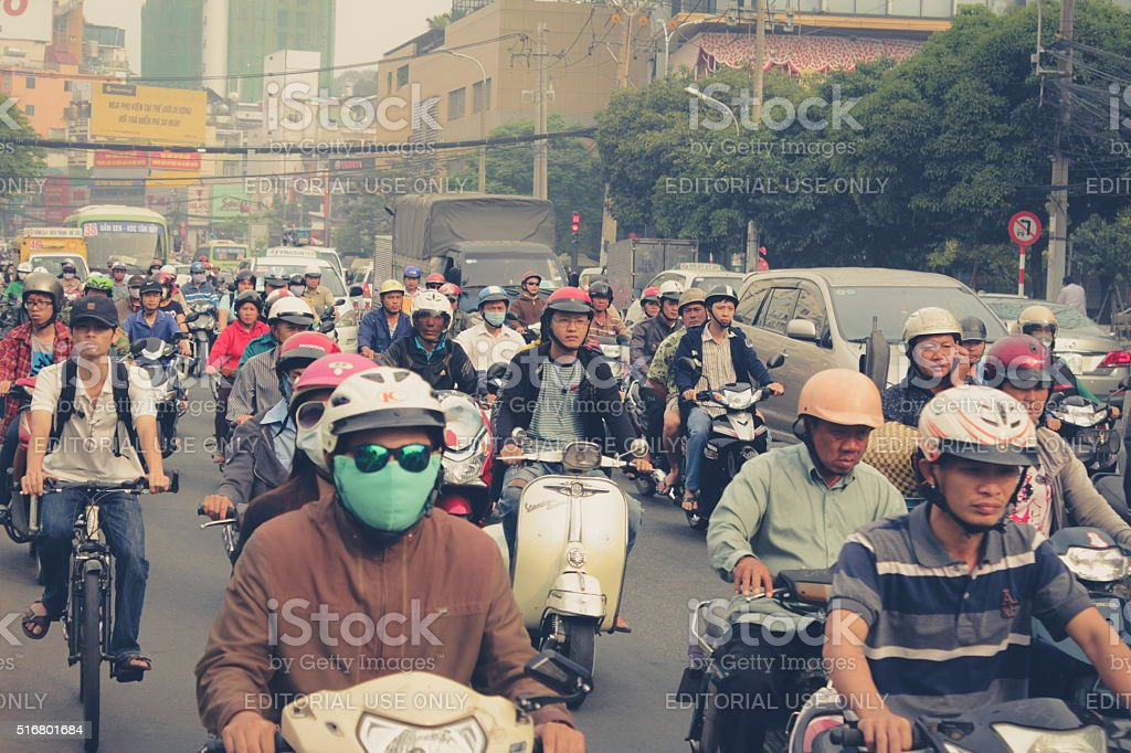Road traffic crowded with motorbikes and scooter drivers. stock photo
