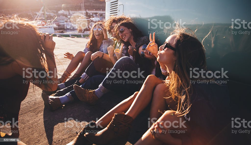 Road Trip Hipster friends showing peace sign while taking picture stock photo