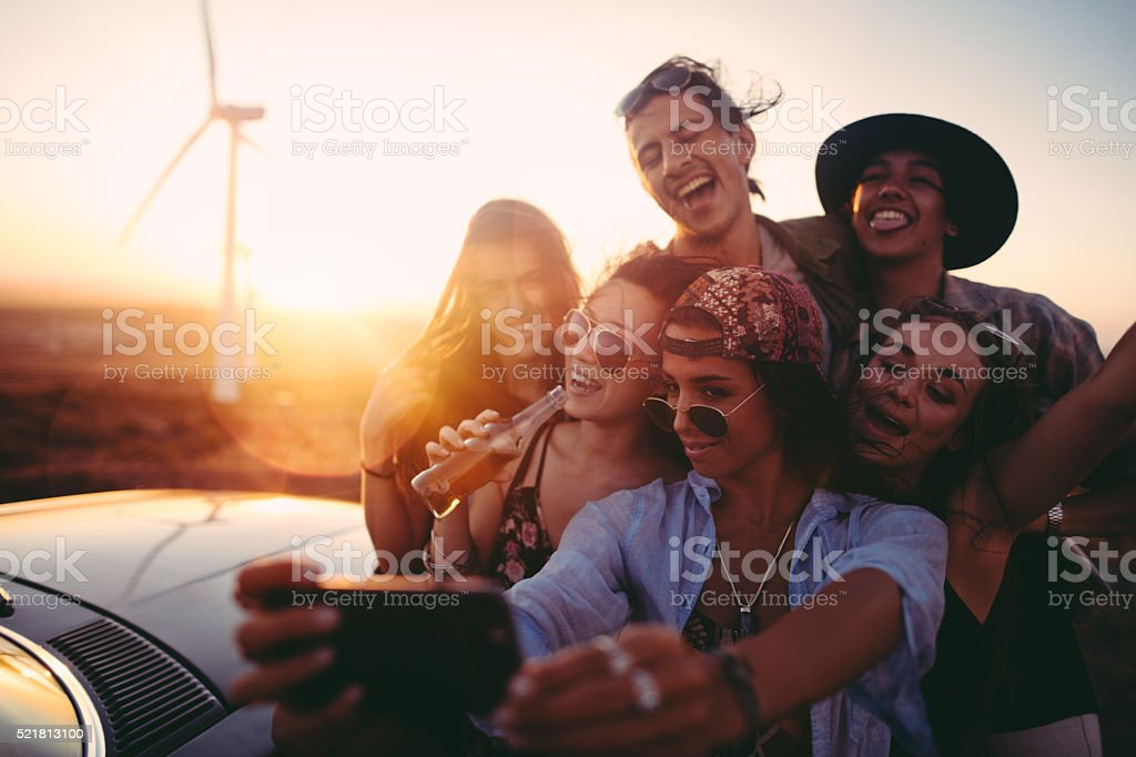 Road Trip hipster friends taking selfie during sunset with phone stock photo