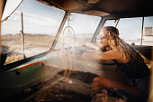Road Trip Hipster Girl Sitting in Retro Van at beach