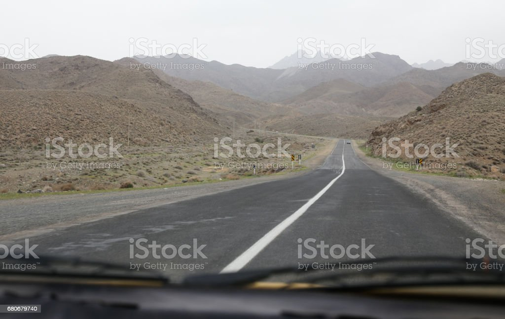 Road view from a car, driving from Tehran to Isfahan (Iran) along side rocky mountains stock photo