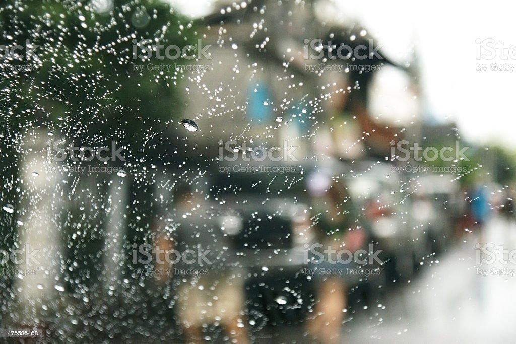 Road view through car window with rain drops stock photo