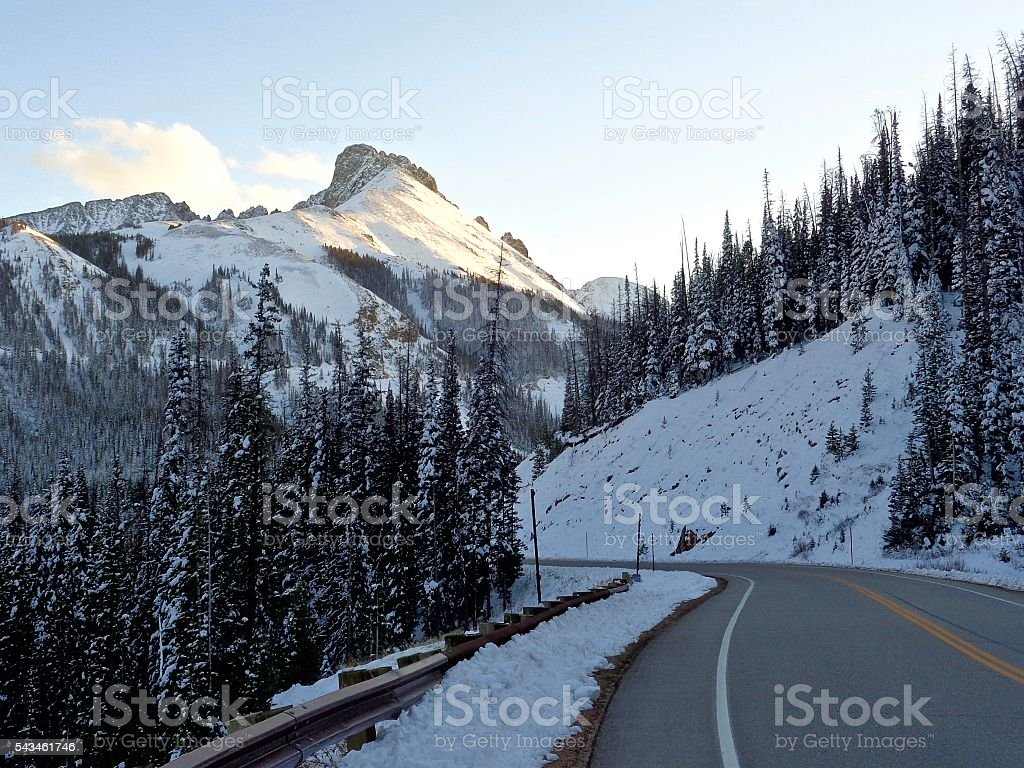 Road winding through wintry, mountainous landscape stock photo