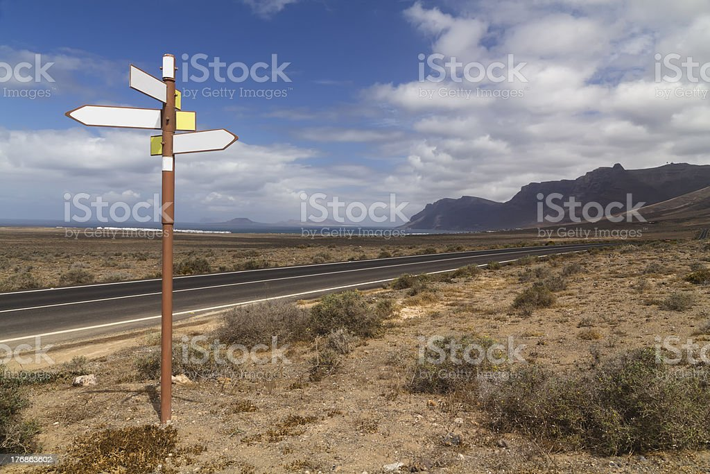 Road with empty directional signs and mountains royalty-free stock photo
