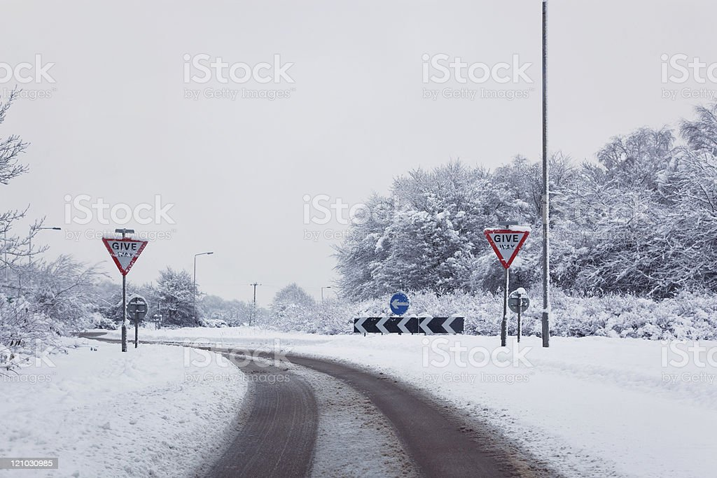 Road with give way signs in the snow royalty-free stock photo