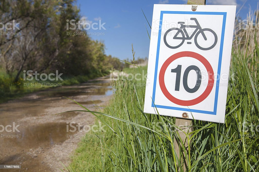 Road with signboard about bicycle speed limitation royalty-free stock photo