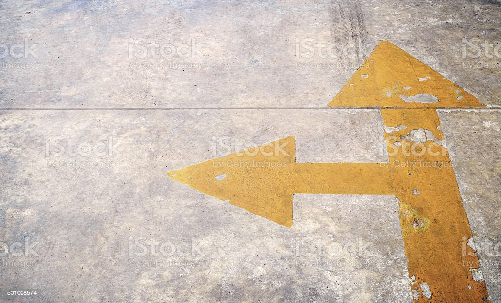 road with yellow arrow on concrete background stock photo